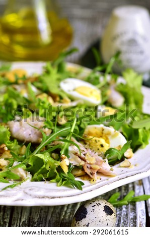 Green salad with chicken,apple and eggs on wooden table.