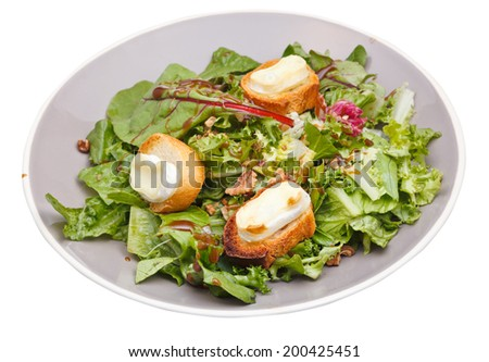 green salad with goat cheese and croutons on plate isolated on white background - stock photo
