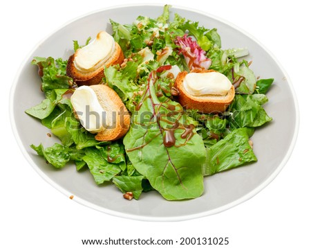 green salad with goat cheese on plate isolated on white background - stock photo