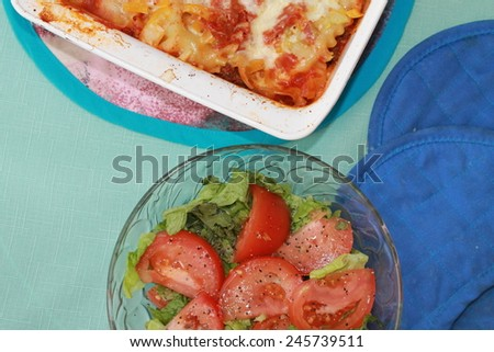 Green salad with hot Lasagna - stock photo