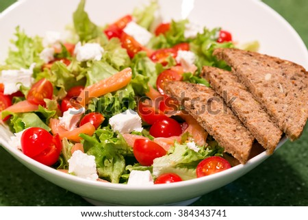 green salad with salmon and tomato with  bread