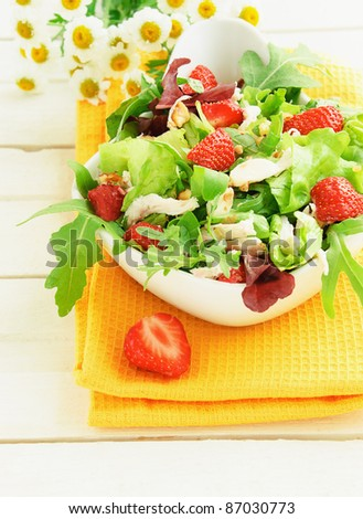 Green salad with strawberry, chicken, nuts, cheese in a white bowl on the table - stock photo