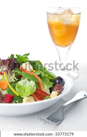 Green salad with vegetables and glass of iced tea