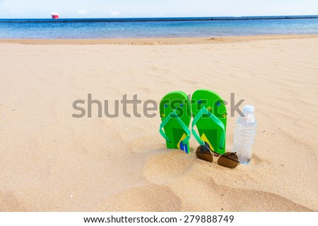 green  sandals  on  beach with bottle of clear water and glasses