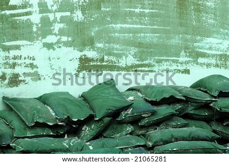 Green sandbags stacked against a green wall - stock photo