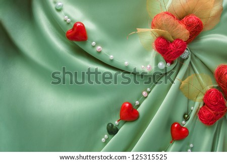 Green satin cloth with red Valentine hearts and empty space - stock photo