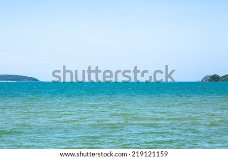 Green sea and small island in sunshine day