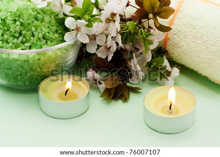 Green sea salt and a lit candle on a green background