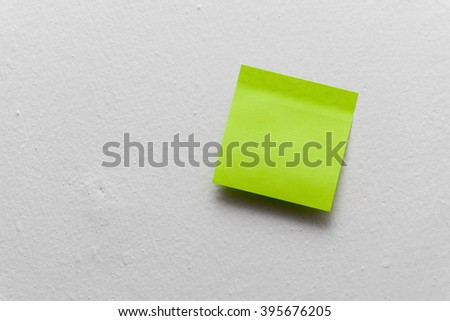 Green self sticky memo little paper on the structured white wall. - stock photo