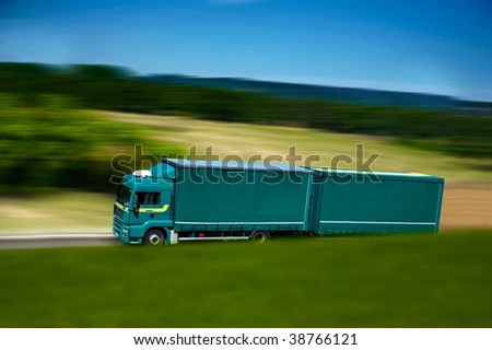 green semi truck and trailer on campain's road - stock photo