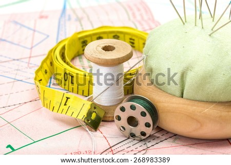 Green sewing accessories and pincushion on pattern cutting - stock photo
