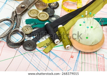 Green sewing accessories on pattern cutting - stock photo