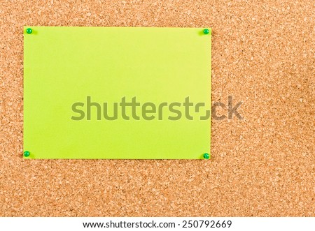 Green sheet of paper attached to corkboard buttons - stock photo