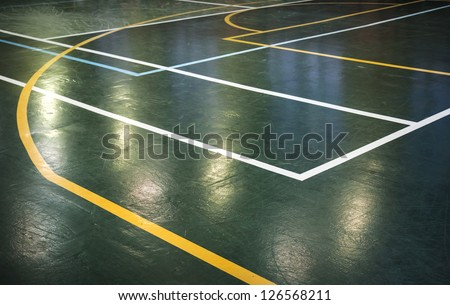 Green shining floor of sports hall with marking lines - stock photo