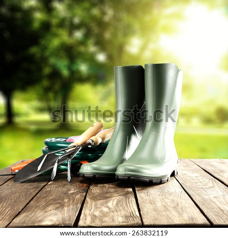 green shoes and garden tools on worn old table space in sun light  - stock photo
