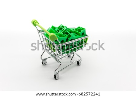 Green shopping cart with green 3d puzzle inside. Go Green concept.