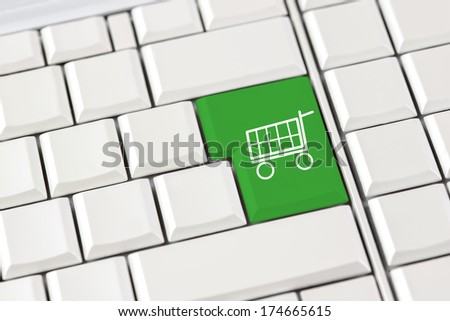 Green shopping trolley icon on a computer keyboard conceptual of e-commerce and online shopping over the internet - stock photo