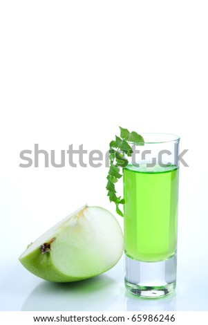 Green shot of absinthe  with apple and herb isolated on a white background - stock photo