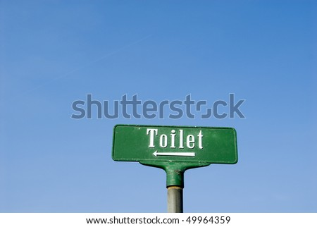 Green sign toilet against a blue sky. Isolated. - stock photo