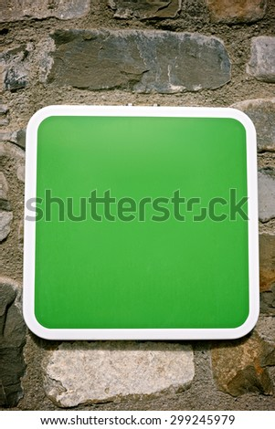 Green signal on a stone wall.