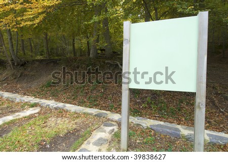 green signboard in a forest - stock photo