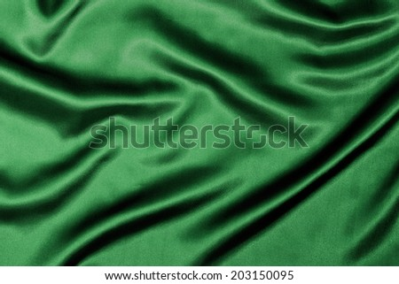 Green Silk background texture with wavy ripples to enhance the sheen of the fabric. - stock photo