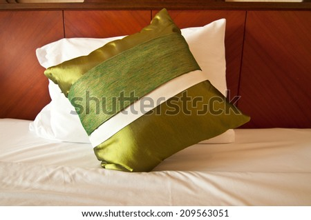 Green silk pillows on white bed - stock photo