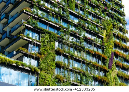 Green skyscraper building with plants growing on the facade. Ecology and green living in city, urban environment concept. Park in the sky, One central park building, Sydney, Australia