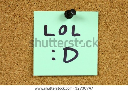 Green small sticky note on an office cork bulletin board. LOL internet acronym with happy emoticon. Internet fun. - stock photo