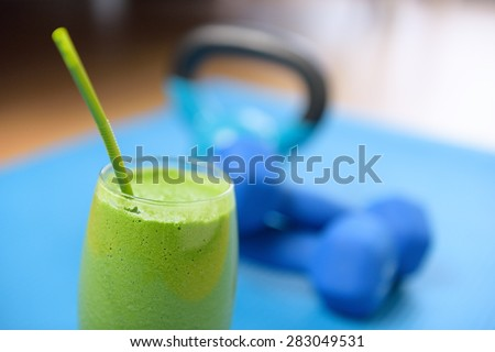 Green smoothie and dumbbells weights on yoga mat at the gym - fitness concept. Clean eating and detox with vegetable and spinach drink as part of the latest food trend in living healthy. - stock photo