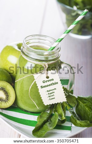 Green smoothie and fresh ingredients on a white wooden background - stock photo