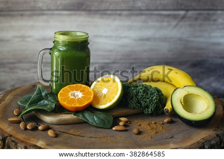 Green smoothie and ingredients on a wooden table: spinach, kale, orange, tangerine, bananas, cinnamon and avocado. - stock photo