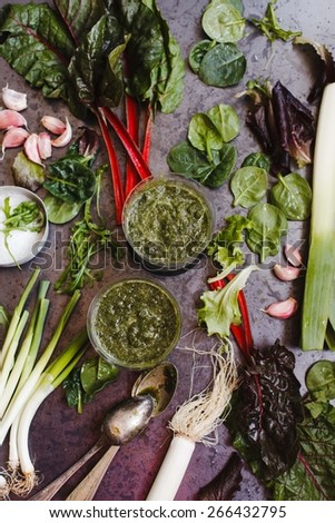 Green smoothie and veggies over on dark metal table.Fresh vegetables: Swiss chard, green onions, bunch of wild garlic, leaves of spinach, garlic, leek. Low key.  - stock photo