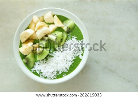 Green smoothie bowl with bananas, fresh kiwi and shredded coconut on a white marble background - stock photo