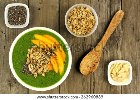 Green smoothie bowl with mangoes, granola, almonds and chia seeds, overhead scene on wood - stock photo