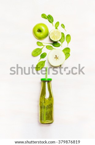 Green smoothie drink in bottle with straw  and  ingredients ( spinach,apple, lime )  on white wooden background, top view - stock photo