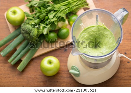 Green smoothie in a blender and ingredients, view from above - stock photo