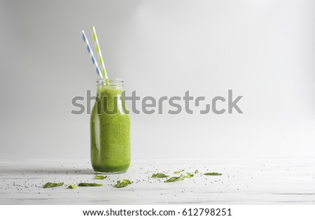 Green smoothie in a glass bottle