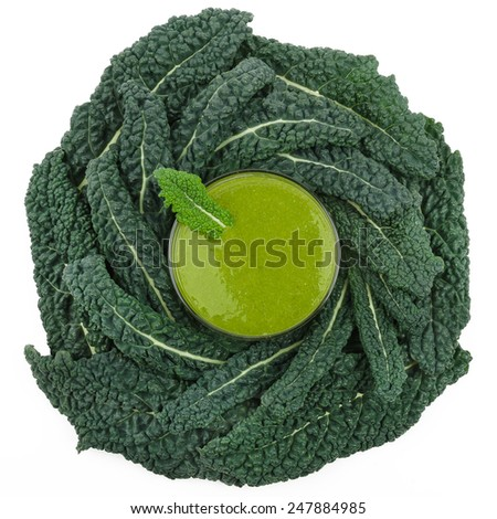 Green smoothie in a glass placed in a bed of kale, photographed from above. A raw, healthy and vegan drink made of green leafs and fruits. - stock photo