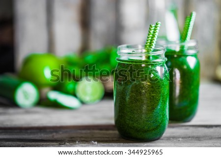 Green smoothie on rustic wooden background - stock photo