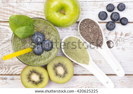Green smoothie with young barley, chia seeds and blueberries on white, wooden background, top view - stock photo