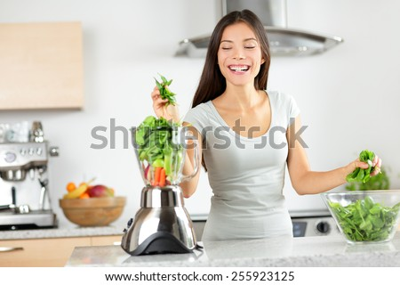 Green smoothie woman making vegetable smoothies with blender home in kitchen. Healthy eating lifestyle concept portrait of beautiful young woman preparing drink with spinach, carrots, celery etc. - stock photo