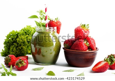 Green smoothies from apple, spinach and cucumbers in a glass jar on a white background. Next fresh strawberries. The lettuce in the background. Detox concept. Useful and tasty non-alcoholic beverages - stock photo