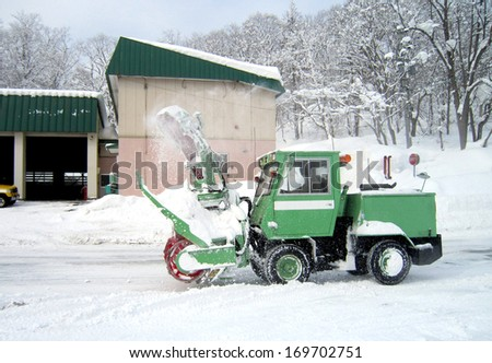 green snow truck on snowy road - stock photo