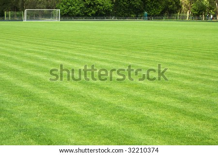 Green soccer field and goal at a distance - stock photo