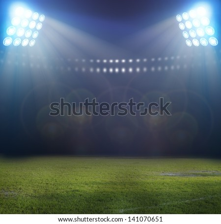 Green soccer field, bright spotlights, - stock photo