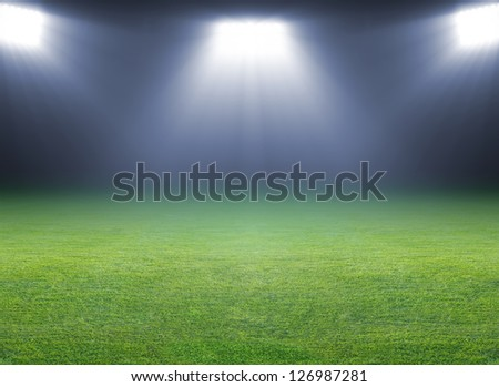Green soccer field, bright spotlights, illuminated stadium - stock photo