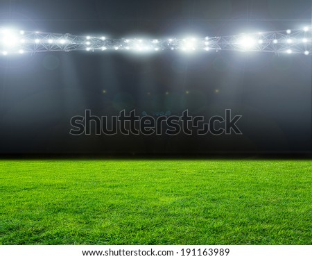 Green soccer field, bright spotlights, illuminated stadium  - stock photo