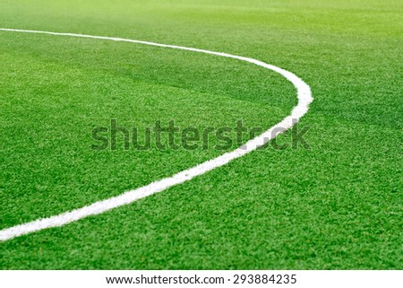 Green soccer field grass with white mark line, soft focus - stock photo