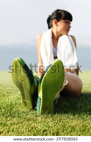 green sole of shoes on grass, tired sportswoman - stock photo